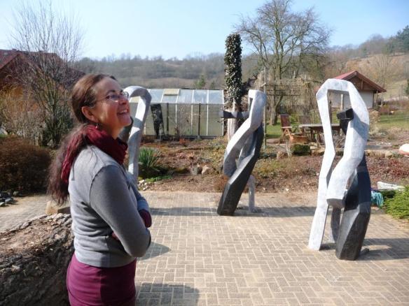 """""""Gegenläufiger Tanz"""". Beate Debus vor ihrem Atelier im stillen Dialog mit ihren Skulpturen."""